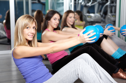 Group of friends in a fitness class using a medicine balls